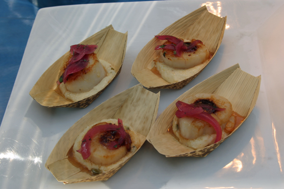 Scallop on a bed of polenta topped with marinated red onion