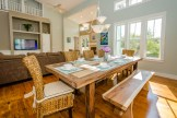 A solid hardwood farm-style dining table anchors the main living space.