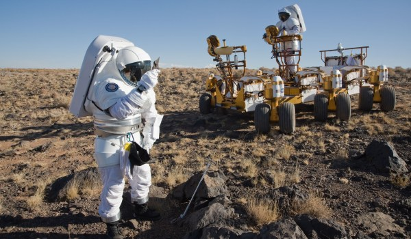 An astroanut and geologist test a rover in a 2008 Desert RATS study. (Credits: NASA).