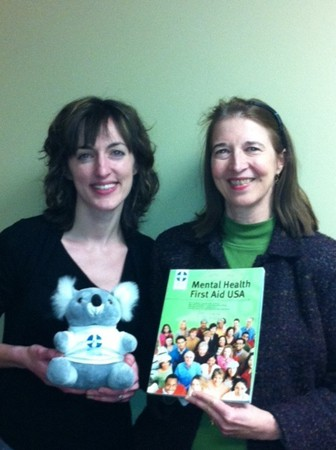 NAMI Minnesota's criminal justice director, Anna McLafferty (left), and  their older adults program director and development officer, Kay King, are certified Mental Health First Aid instructors. The koala bear is the class mascot, Algee, named after the first-aid acronym taught to students in the class. He is a koala because the class originated in Australia. Photo courtesy of NAMI Minnesota