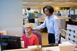 Bev Lambkins (right) assists her employee Marquita Laidlaw (left) with a call from a CenterPoint  Energy customer.