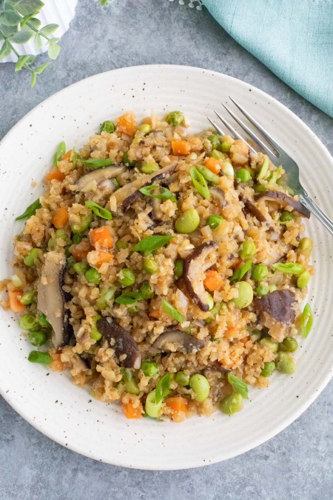 Ginger cauliflower fried rice will satisfy you craving for chinese food without making you overload on carbs! Loaded with veggies and fresh ginger, this dish will quickly become a family favorite that's ready in 30-minutes! Gluten-free & dairy-free.