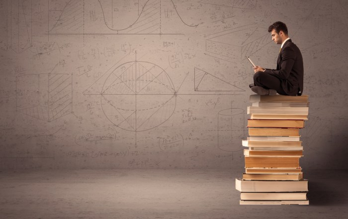 Businessman with tablet sitting on books