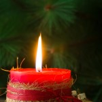 Red Christmas candle and Christmas ornaments on wood