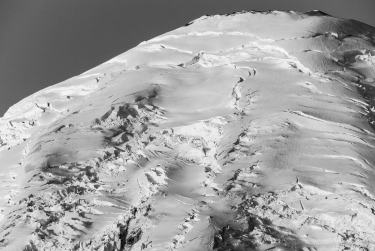A black and white photograph of the early morning autumn sun shining on a closeup view of the summit of Mt Rainier. Viewed from the Sunrise area at Mount Rainier National Park, Washington.