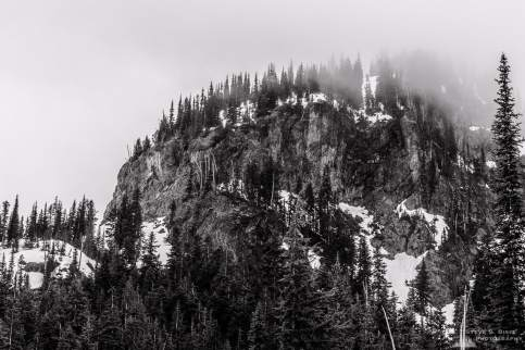 A black and white landscape photograph of a cloud shrouded Crystal Peak as viewed from lower Crystal Lake in the Mount Rainier National Park, Washington.