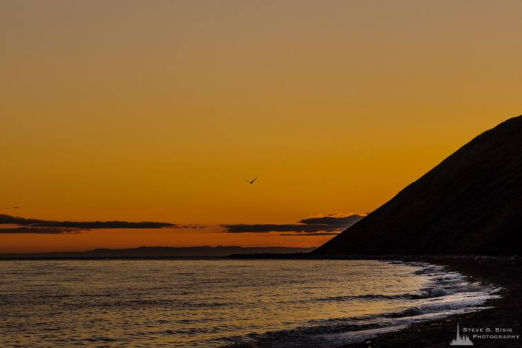 A landscape photograph of the Summer setting sun behind the bluffs at Ebey's Landing on Whidbey Island near Coupeville, Washington.