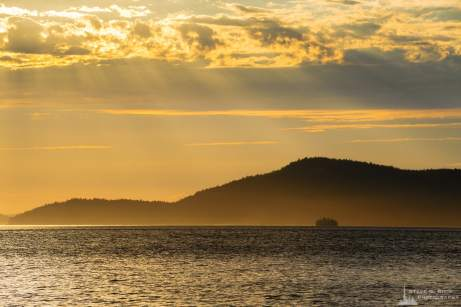 A photograph of evening sun rays breaking through the clouds over Rosario Strait and the San Juan Islands as seen from Washington Park in Anacortes, Washington.