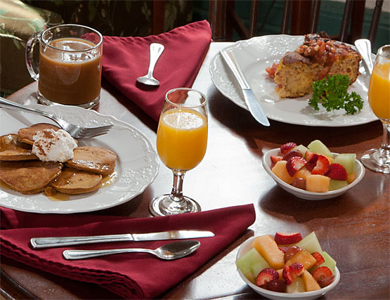 Breakfast plates with pancakes, quiche, fresh fruit