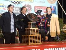 "Tanner Thorson of Minden, Nev. kisses the ""Aggie"" trophy after winning the 2015 ""Turkey Night Grand Prix"" at Perris (Calif.) Auto Speedway as Cary, Chris, and J.C. Agajanian, Jr. look on."