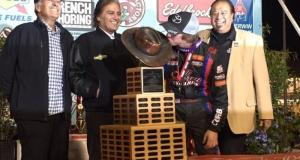 """Tanner Thorson of Minden, Nev. kisses the """"Aggie"""" trophy after winning the 2015 """"Turkey Night Grand Prix"""" at Perris (Calif.) Auto Speedway as Cary, Chris, and J.C. Agajanian, Jr. look on."""