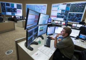In this Wednesday, May 20, 2015 photo, system control center operator Ryan Cox sits at his computer workstation at an AEP Transmission Operations Center in New Albany, Ohio. Like most big utilities, AEP's power plants, substations and other vital equipment are managed by a network that is separated from the companyís business software with layers of authentication, and is not accessible via the Internet. Creating that separation, and making sure that separation is maintained, is among the most important things utilities can do to protect the grid's physical assets. (AP Photo/John Minchillo)