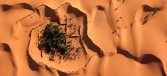 Aerial view of Ain Hamou and adjacent villages where gardens are in hollows between the dunes that are capped with rows of palm fronds to keep the sand from burying the plants.  Water was traditionally brought up from hand dug wells with ropes and pulleys, but now electric pumps do the work.