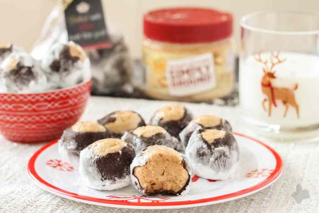 Creamy with a little bit of crunch, Peter Pan® Simply Ground Peanut Butter works beautifully in these Puppy Chow Truffles. Peanut butter balls dipped in chocolate and rolled in powdered sugar are the perfect treat to pass out to all your friends, family and coworkers this holiday season. Bonus-free printable holiday cookie gift tag! No excuses! | Strawberry Blondie Kitchen