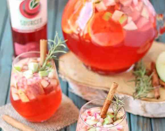 A delicious blend of cranberries, apples, cinnamon, rosemary and seasonal fruits make this Cranberry Apple Rosemary Sangria the go to cocktail of Autumn. | Strawberry Blondie Kitchen