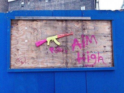 "a toy AK47 gun and the words ""aim high"" appear in this NYC street art"