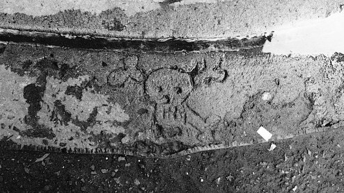 the image of a skull carved into the sidewalk