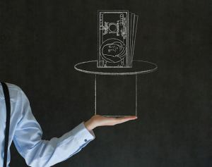 Business man, student or teacher pulling money from a magic hat on blackboard background
