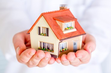 House in human hands on a white background