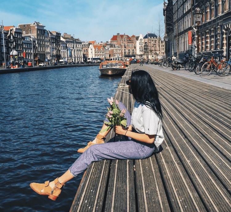 amsterdam canals bloemenmarkt girl champion flowers city travel blogger