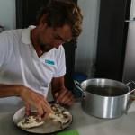 Skippern renser en revfisk for bein, og lager fishballs