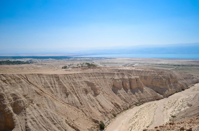 The caves of Qumran far below where the Dead Sea Scrolls were discovered. And beyond, a glimmering bit of the Dead Sea.