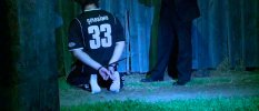 Still image taken from video of a man detained by police during a raid kneeling on the ground in Sydney