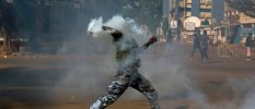 An anti-government protester throws a tear gas canister at riot police in Ouagadougou