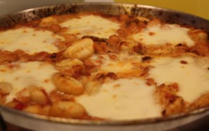gnochi and prawns in bacon and tomato sauce with melted mozarella on top