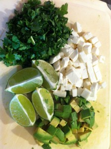 The condiment tray. clockwise from top: chopped cilantro, queso fresco, chopped avocado, limes.