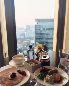 Breakfast with a view in Seoul! I had a mix of Asian and Western breakfast, with japchae, dim sum, dragonfruit, and abalone porridge alongside pancakes. Yes all the food pictured was for me #twmdtravels