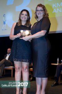 Meire Alessandra, diretora comercial da Momento Editorial, entrega o troféu para Taís Massari, gerente comercial da Khomp.