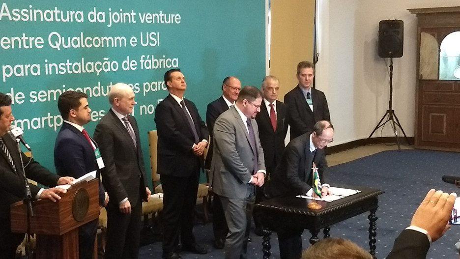 C.Y. Wei, da USI, assina o contrato de criação da joint venture com a Qualccom. A seu Lado, Cristiano Amon, presidente da Qualcomm. Ao fundo, entre as autoridades presentes, estavam Gilberto Kassab (MCTIC) e Geraldo Alckimin (Governo de São Paulo)