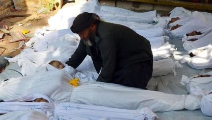 A man holds the body of a child allegedly killed by a nerve gas attack in Syria.