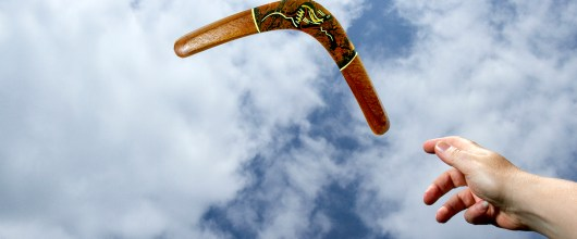 Throwing a painted, wooden boomerang midair with blue sky and cloud background.