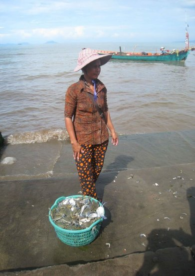 Kep women stands beside her basket of crabs ready for sale.