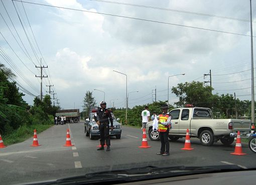 Thai police officer controlling bypassing traffic at the scene of a road accident involving a truck on Bang Na