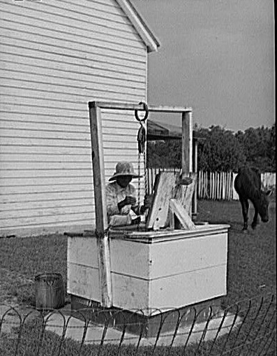 Farmer drawing water from well in Ridge, Md., St. Mary's County, circa 1935