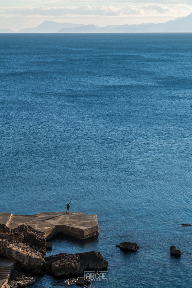 A fisherman throwing his bait into a vast, blue ocean.