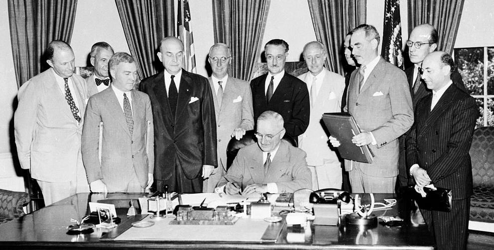 Le président américain Harry S. Truman signe le Traité de l'Atlantique Nord à Washington le 4 avril 1949. Photo de Abbie Rowe (1905-1967).  Juste derrière Truman, l'ambassadeur de France aux Etats-Unis, Henri Bonnet.