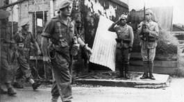 Des hommes d'un Commando du C.L.I. (Corps Léger d'Intervention) en Indochine défilent en septembre 1945 devant des sentinelles japonaises.