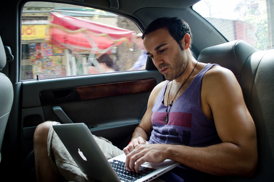 Adrian working on his laptop in the backseat of a car driving through Hanoi.