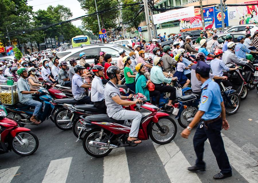 A cluster of motorbikes crossing a major intersection in Ho Chi Minh City, Vietnam.
