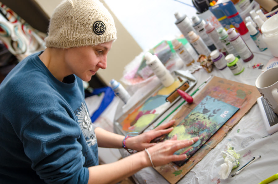 Ashlie at the table working on a painting