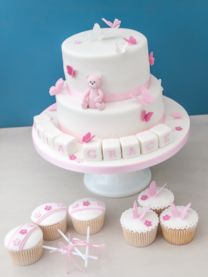 Pink and white Christening cake with themed cupcakes