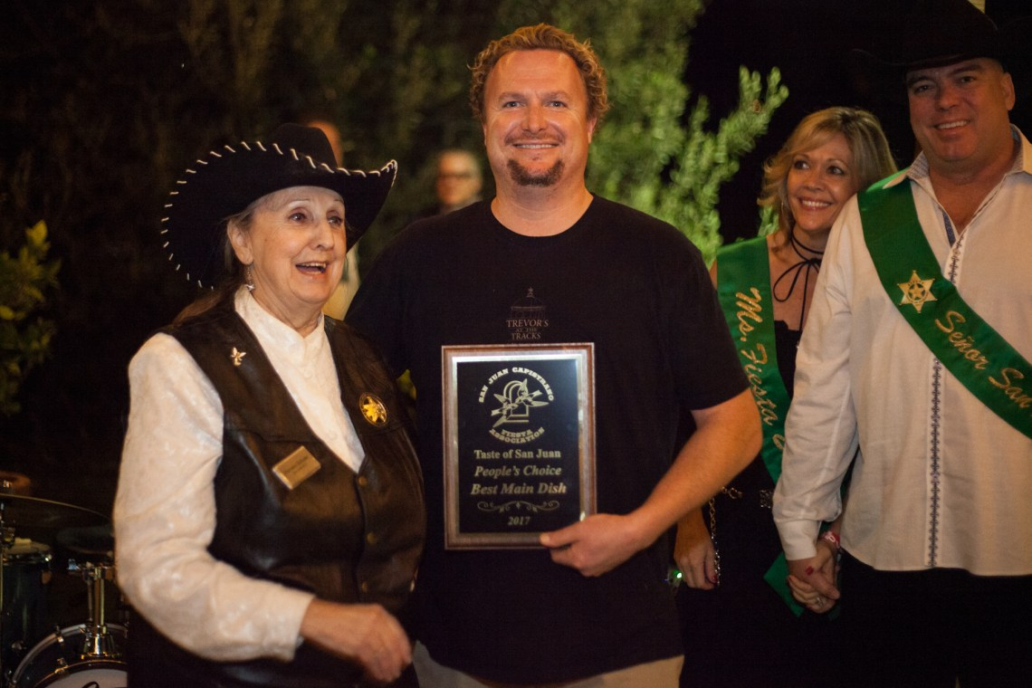 Trevor Baird, owner of Trevor's at the Tracks, accepts the award for best main dish. Photo: Alex Paris