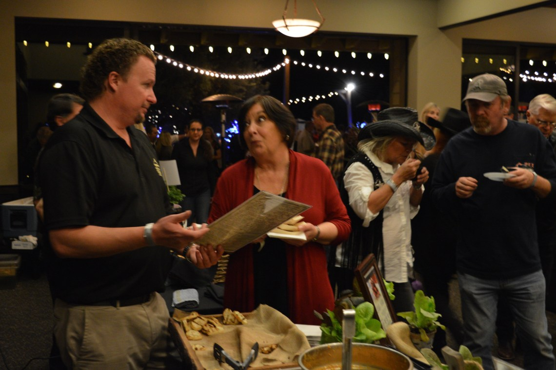 Trevor's At The Track's proprietor, Trevor Baird (left), discusses his restaurant's menu with an attendee of The Taste of San Juan event on Thursday, Feb. 8. Photo: Emily Rasmussen