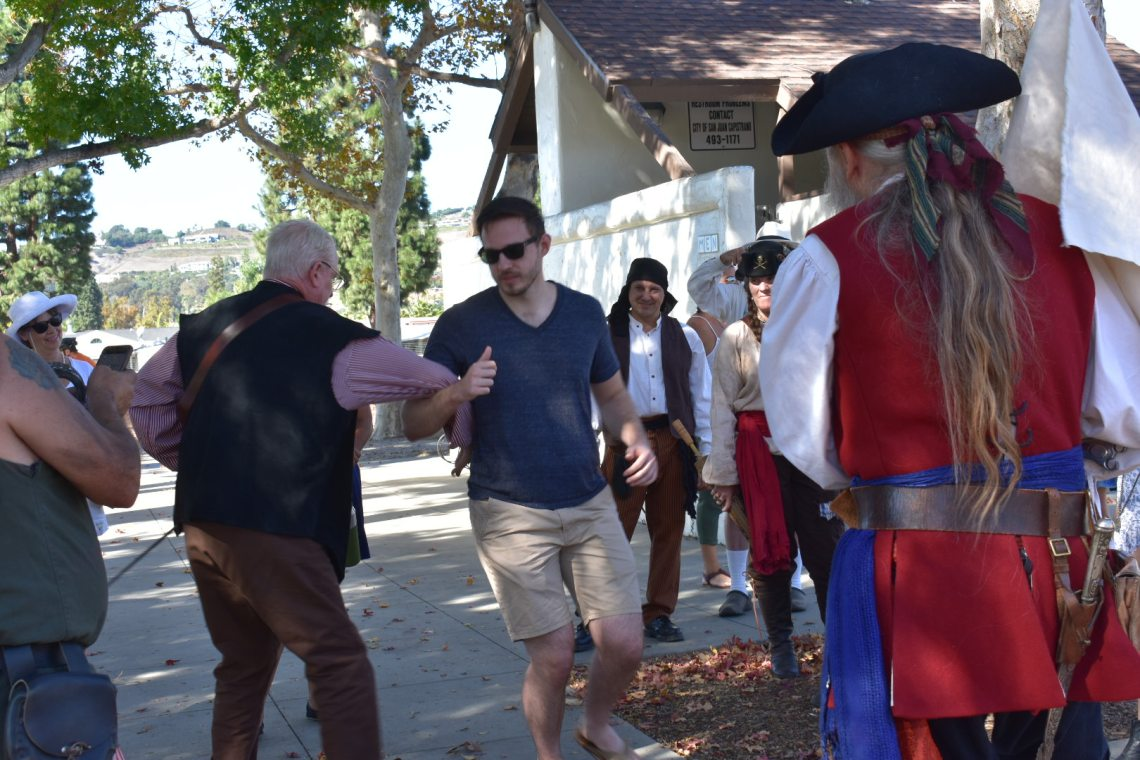 Bob Minty, playing one of the pirates, shows a man how to do a pirate dance at Descanso park on Nov. 3. Photo: Alex Groves