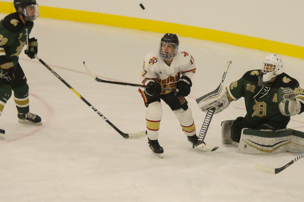 Conor Clarke watches a rebound fly off the Damien goalie on Friday, Feb. 8. Photo: Eric Heinz