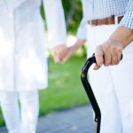 A caregiver holding the hand of her patient while walking outdoors.